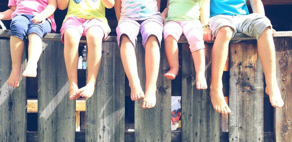 Image of kids feet on fence - Children's Foot Doctor in Sterling VA