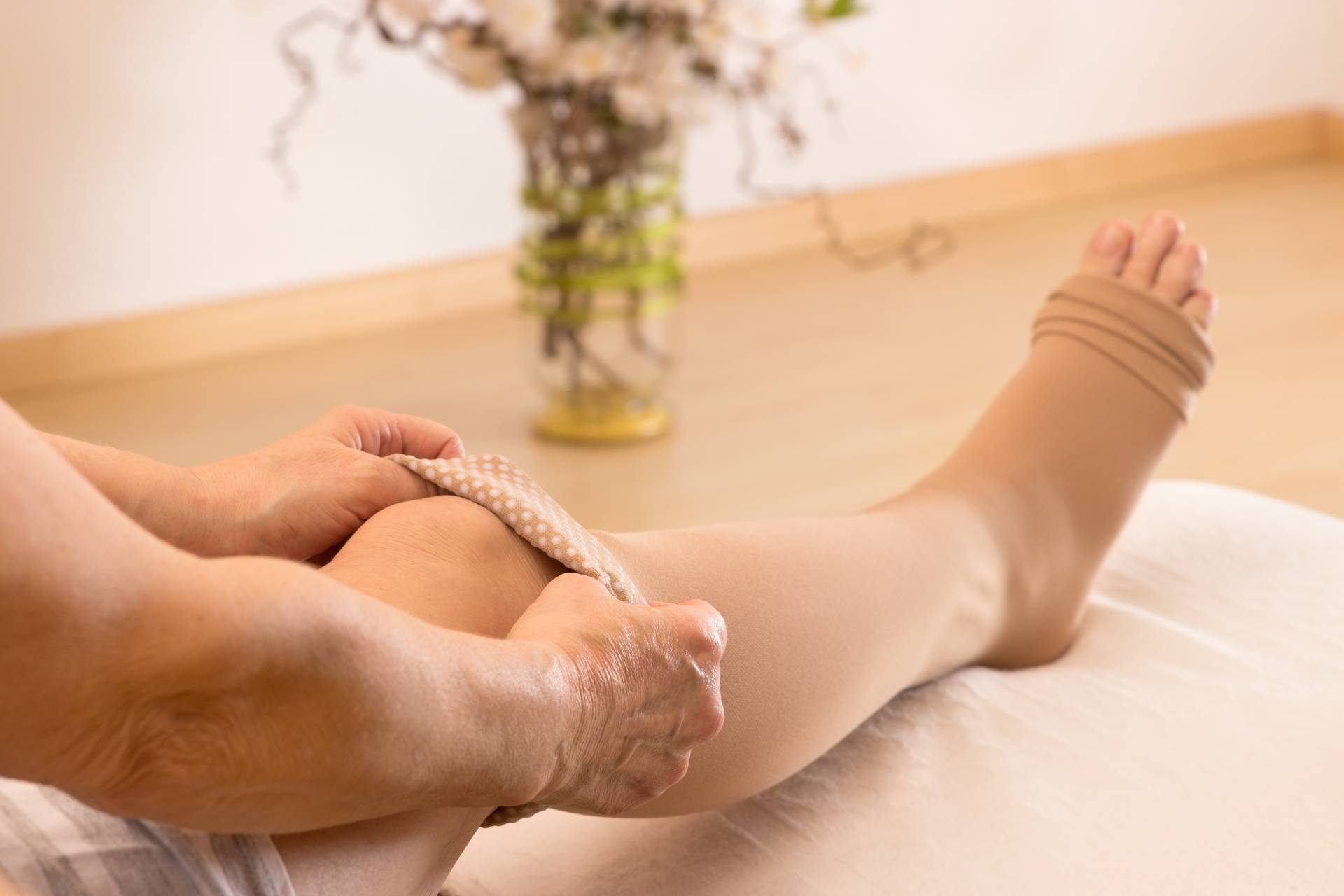 Image of woman putting on compression stockings