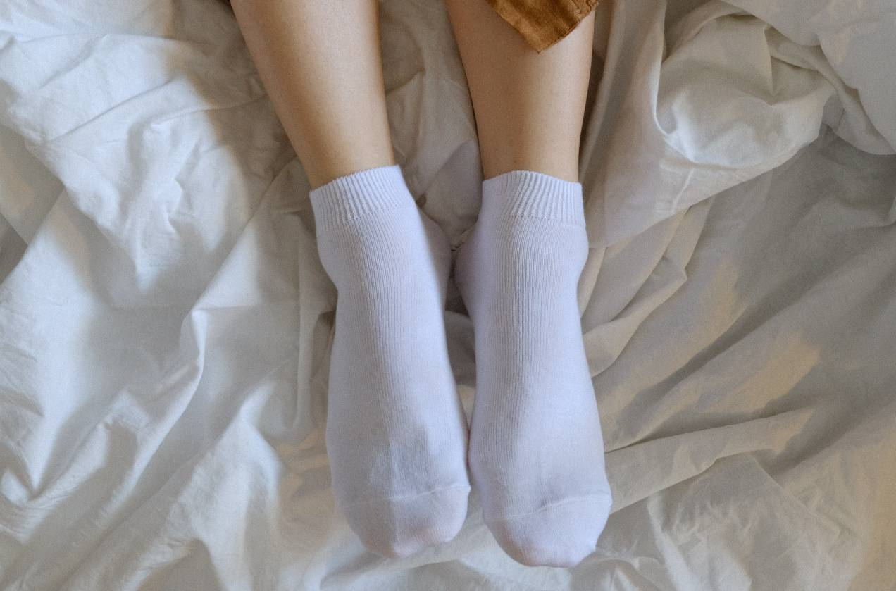 image of socks on feet in bed